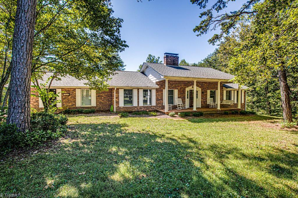 Wonderful all brick home nestled in just under 5 walkable, wooded acres with a continuous flowing stream.  This tranquil country home is only 10 minutes from shopping and entertainment. Step inside to the beautiful new flooring, imagine the fall/winter events you will have around the beautiful stone raised hearth fireplace, vaulted ceiling, great nice open floor design.  Kitchen has island with area for bar stools, abundant counter and cabinet space, granite counters, smooth top ranch on island w/new SS vent hood. Separate laundry room on main. 2 car gara