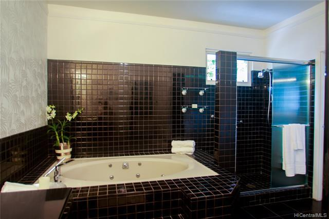 Main Bath houses a jacuzzi tub, shower and great ventilation, designer European custom wallpaper accents.