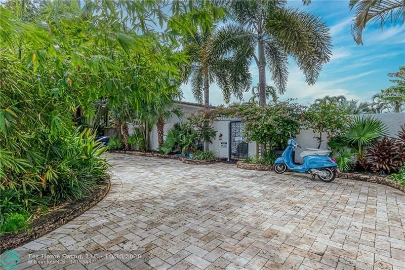 A circular paver driveway leads to this gated courtyard waterfront home.