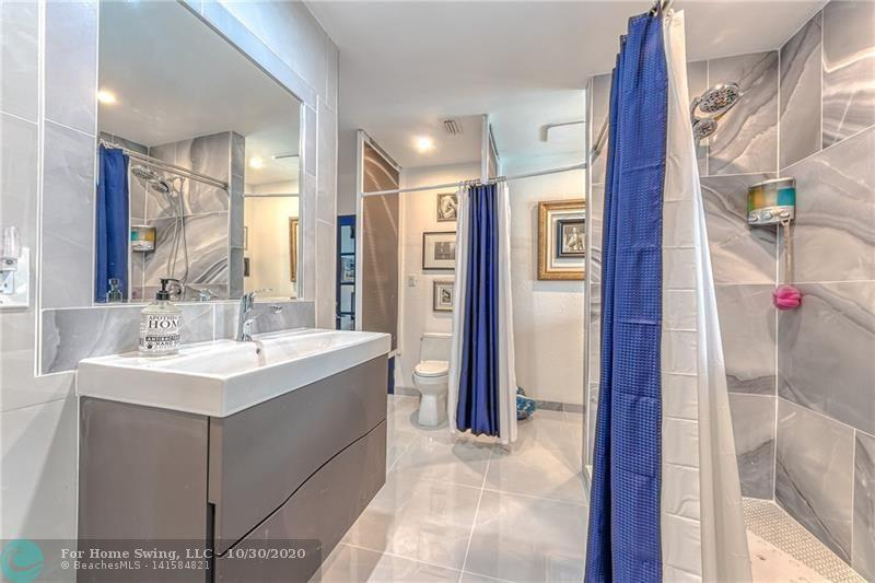 Gym style bathroom with two vanities, two toilets and double showers