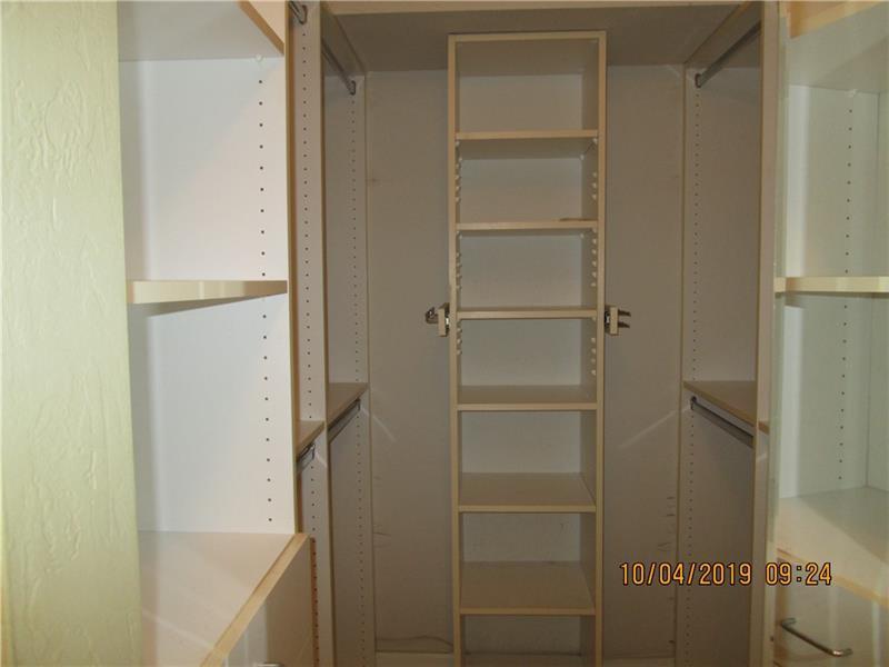 Main bedroom walk in clsoet with custom closet system
