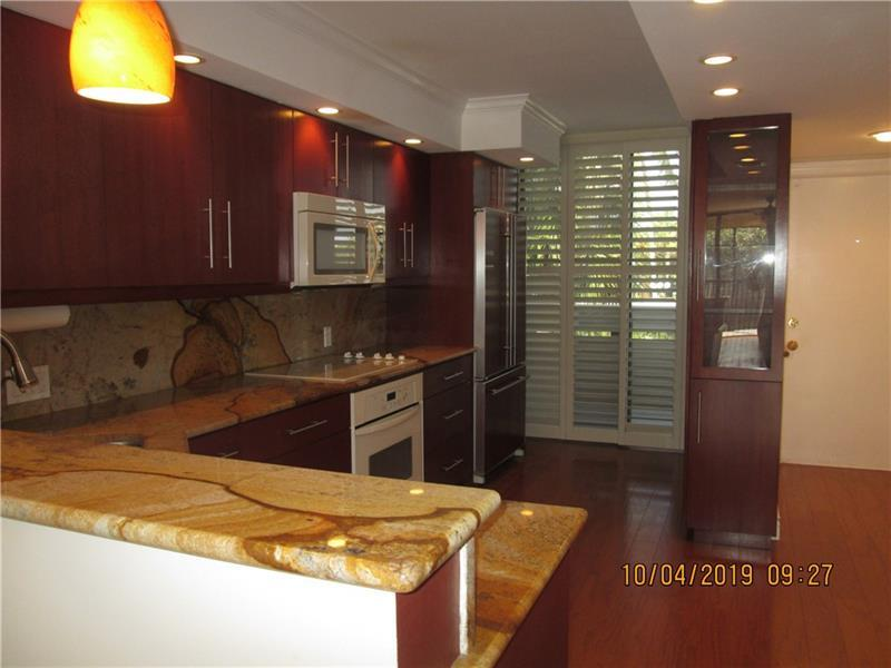 Custom granite in kitchen with extra storage and plantation shutters