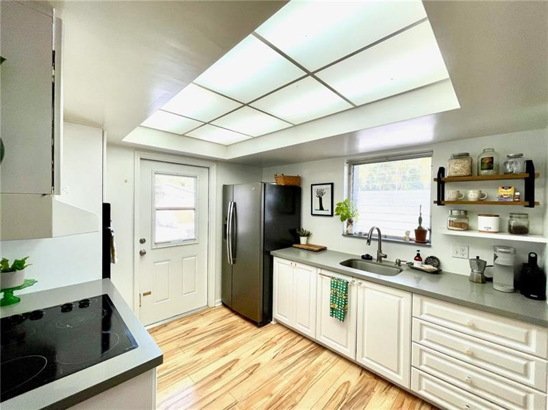 Spacious kitchen with quartz counters and white cabinets