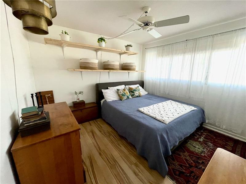 Bedroom features shelving and wood laminate flooring
