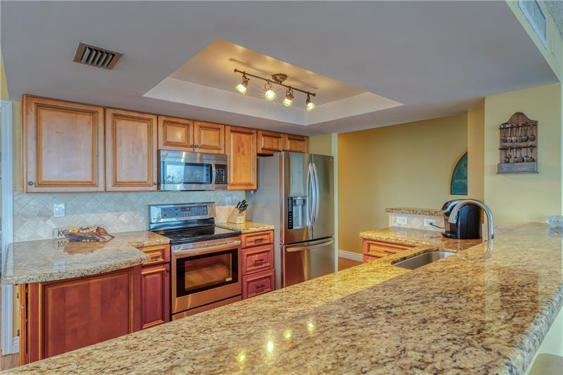 Stainless steel appliances in kitchen with tile backsplash