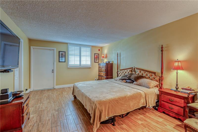 Large master bedroom with wood tile flooring