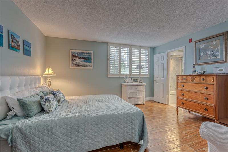 Large bedroom with wood tile flooring