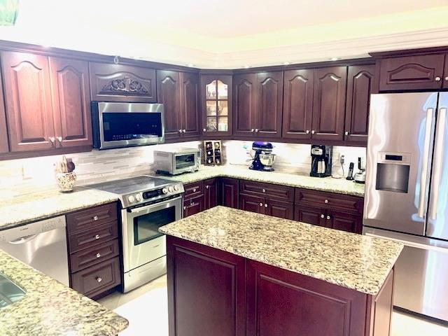 Beautifully remodeled kitchen with custom wood cabinets, with stainless steel appliances, under counter lighting and recessed lighting.