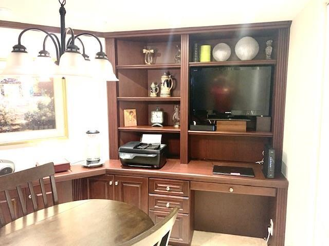 Custom kitchen cabinets continue with an eat-in kitchen area and built-in desk tucked away in the corner.