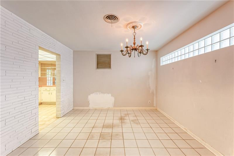 Dining room with tile flooring and entrance into kitchen