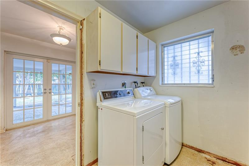 Indoor laundry room with additional storage space and cabinets