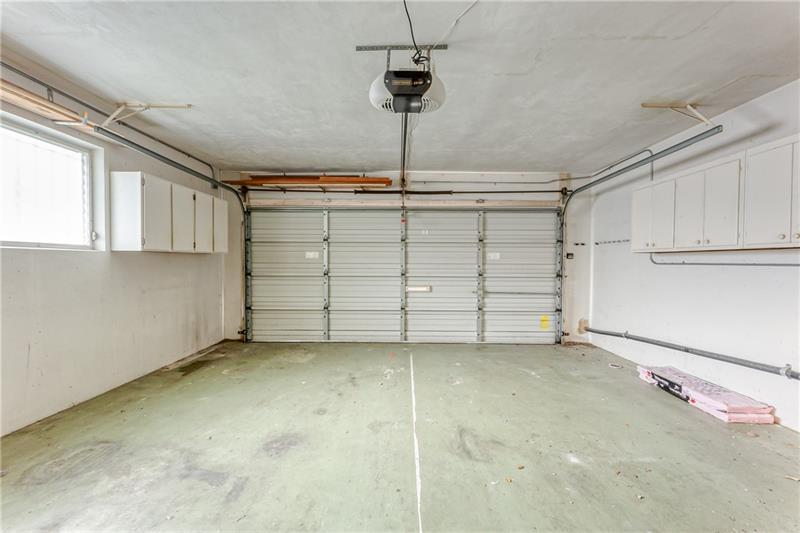 Spacious 2 car garage with storage cabinets