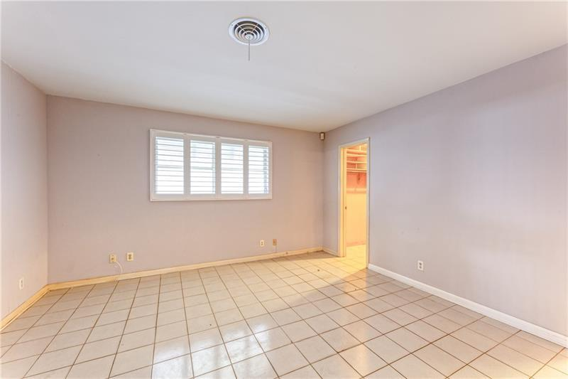 Large master bedroom with tile flooring