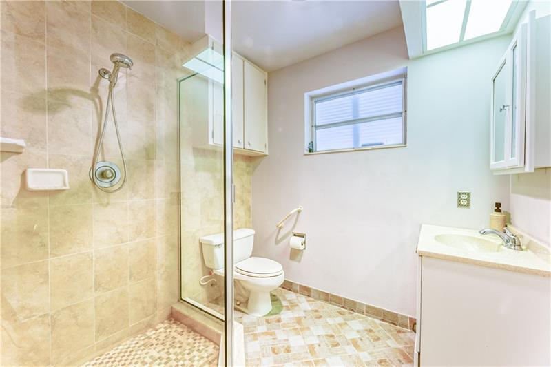 Bathroom with walk in shower and tile