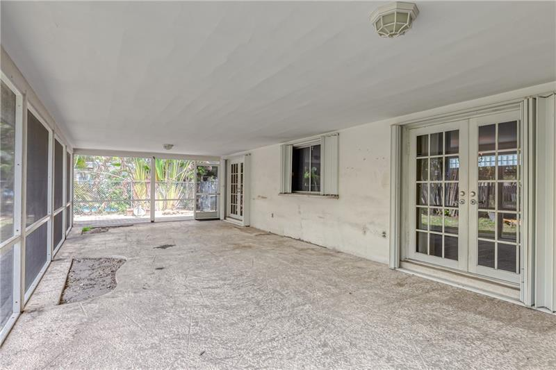 French doors leading out to back covered screen porch and a pass through kitchen window