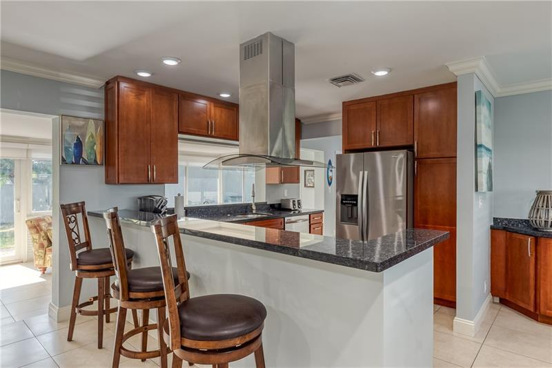 Renovated kitchen with breakfast bar, granite counter tops and stainless steel appliances