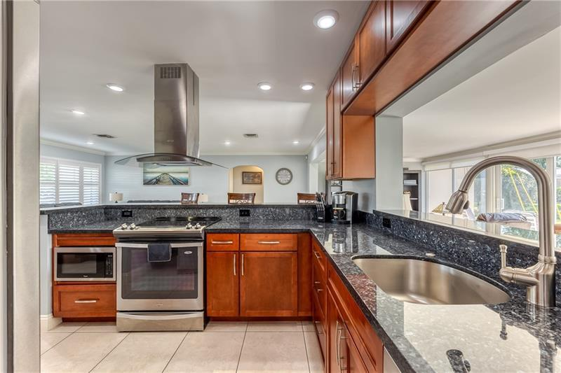 Open kitchen with access and views to living room, dining room and family room