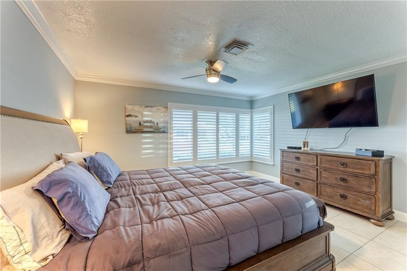 Large master bedroom with crown molding and plantation shutters