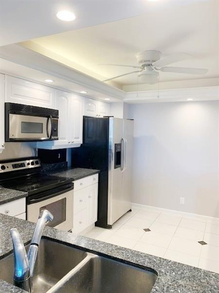 Dome ceiling with recessed lighting in the kitchen.  SS appliances and granite