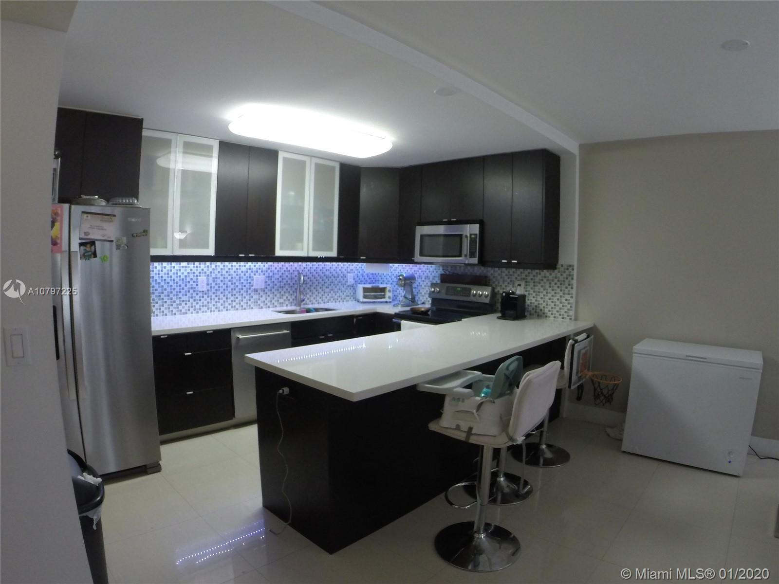 Modern and freshly remodeled kitchen with stainless steel appliances. Gorgeous beige tiling in the b