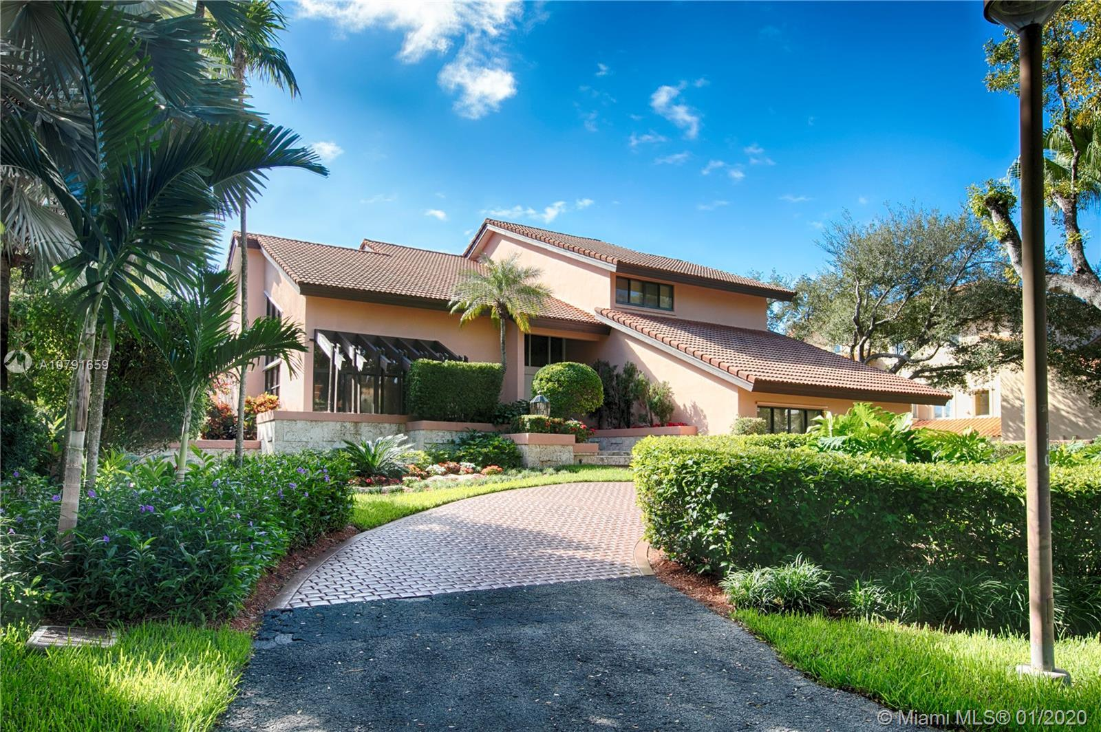 Waterfront 2-story in Islands of Cocoplum. Circular driveway & beautiful landscaping leads to front