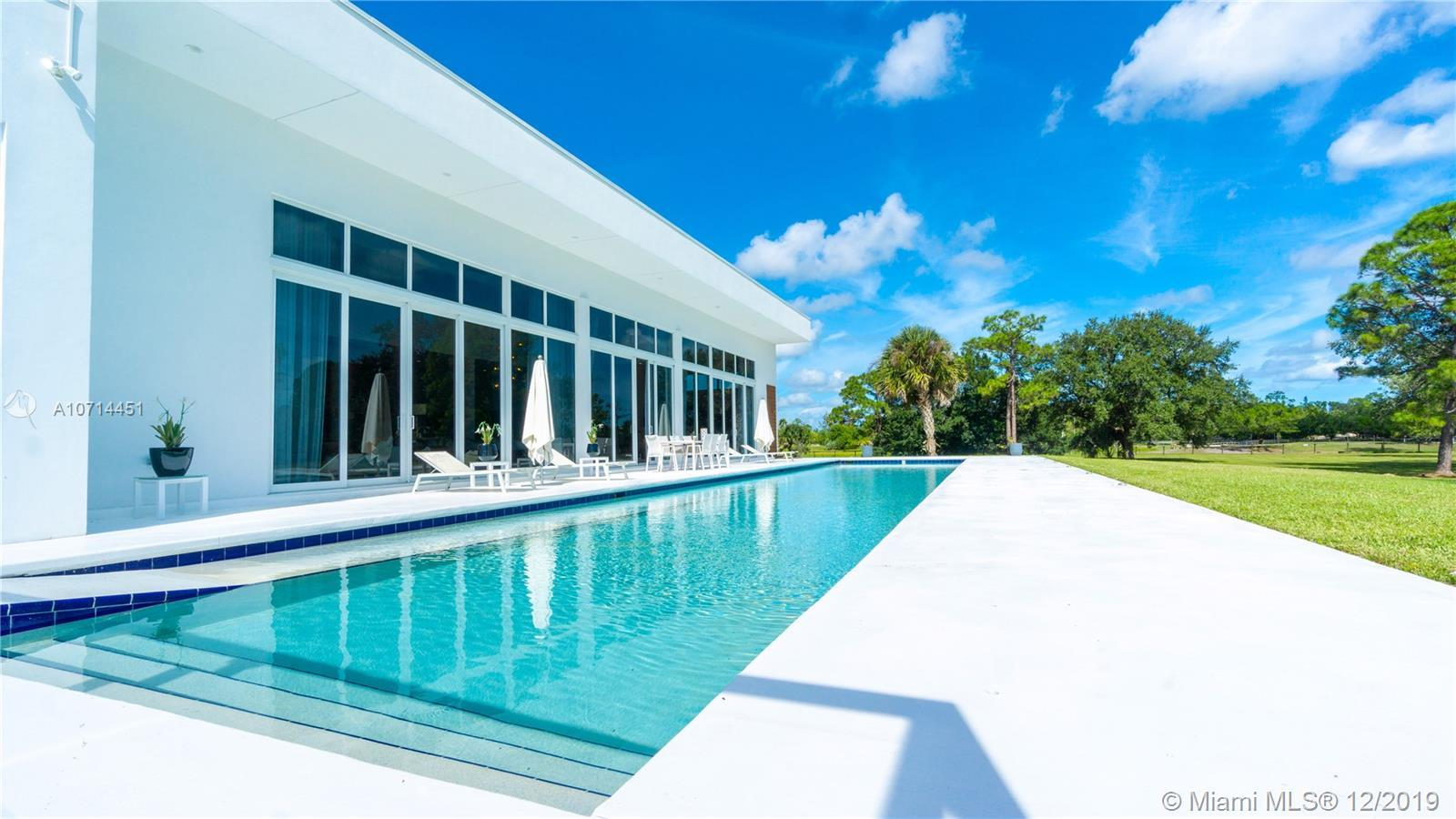 This contemporary, single story estate sits on 20 acres in the exclusive, horse friendly and guard g