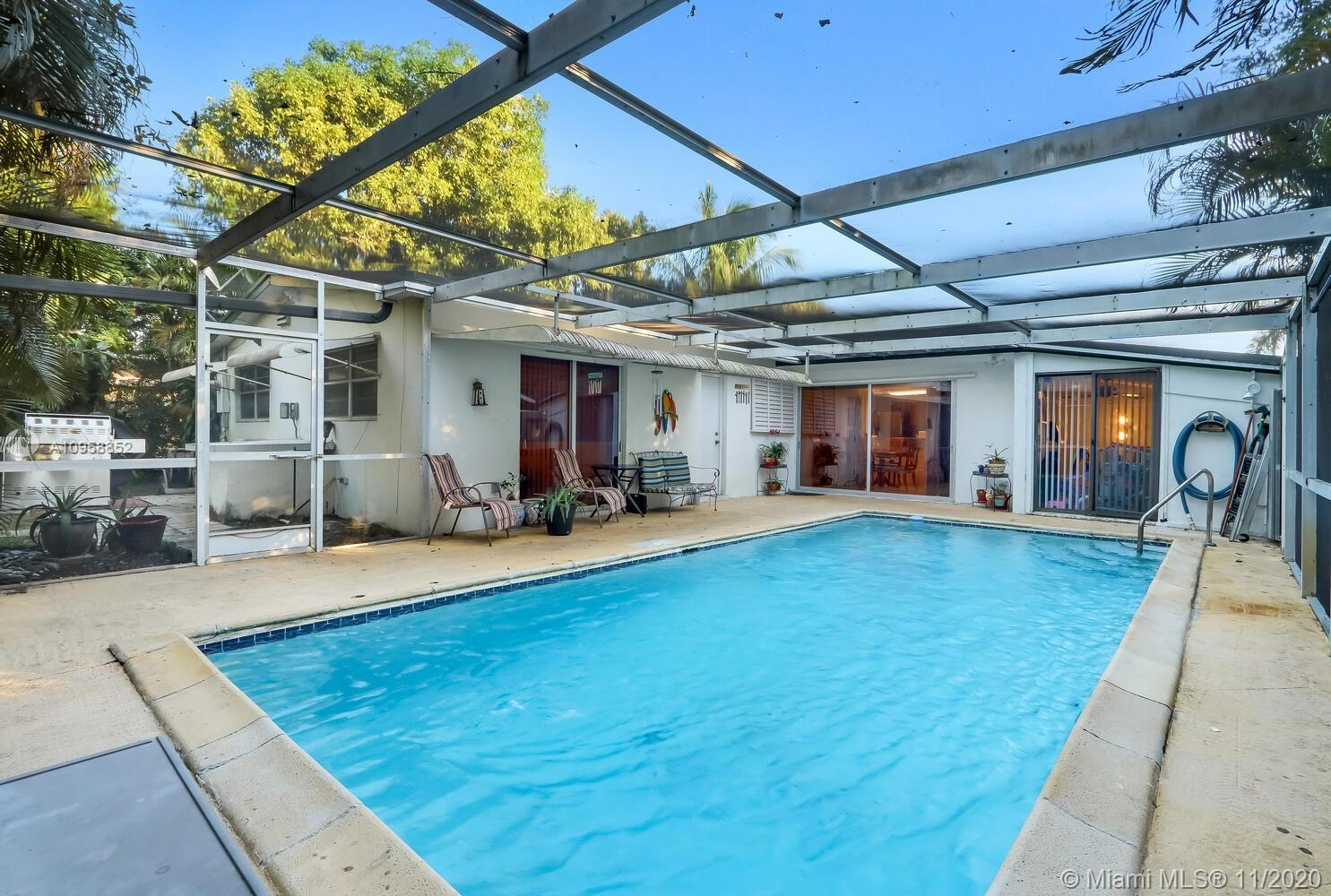 Traditional Florida Pool Home with a charming entryway porch in Hollywood. This 3BD/2BA home has a g