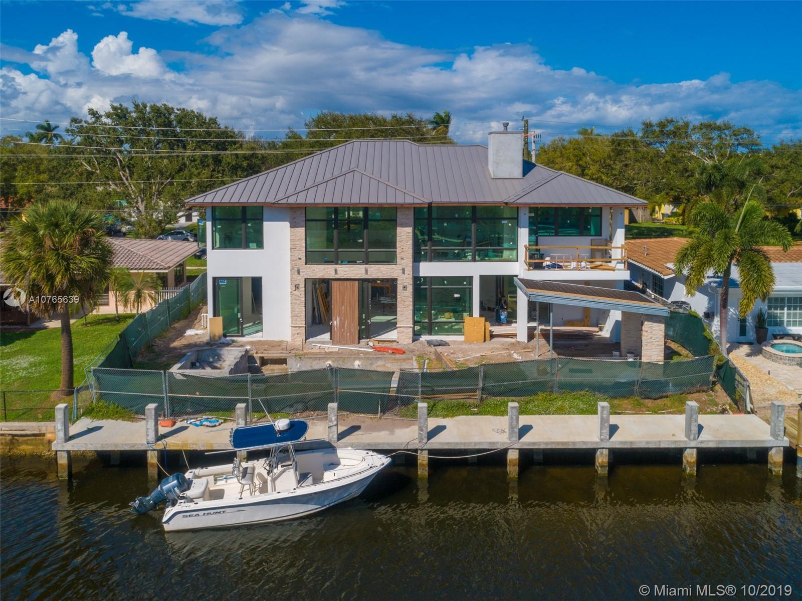 This BRAND NEW, impeccably designed ~5,500sf chic modern estate sits on 80ft of prime water frontage
