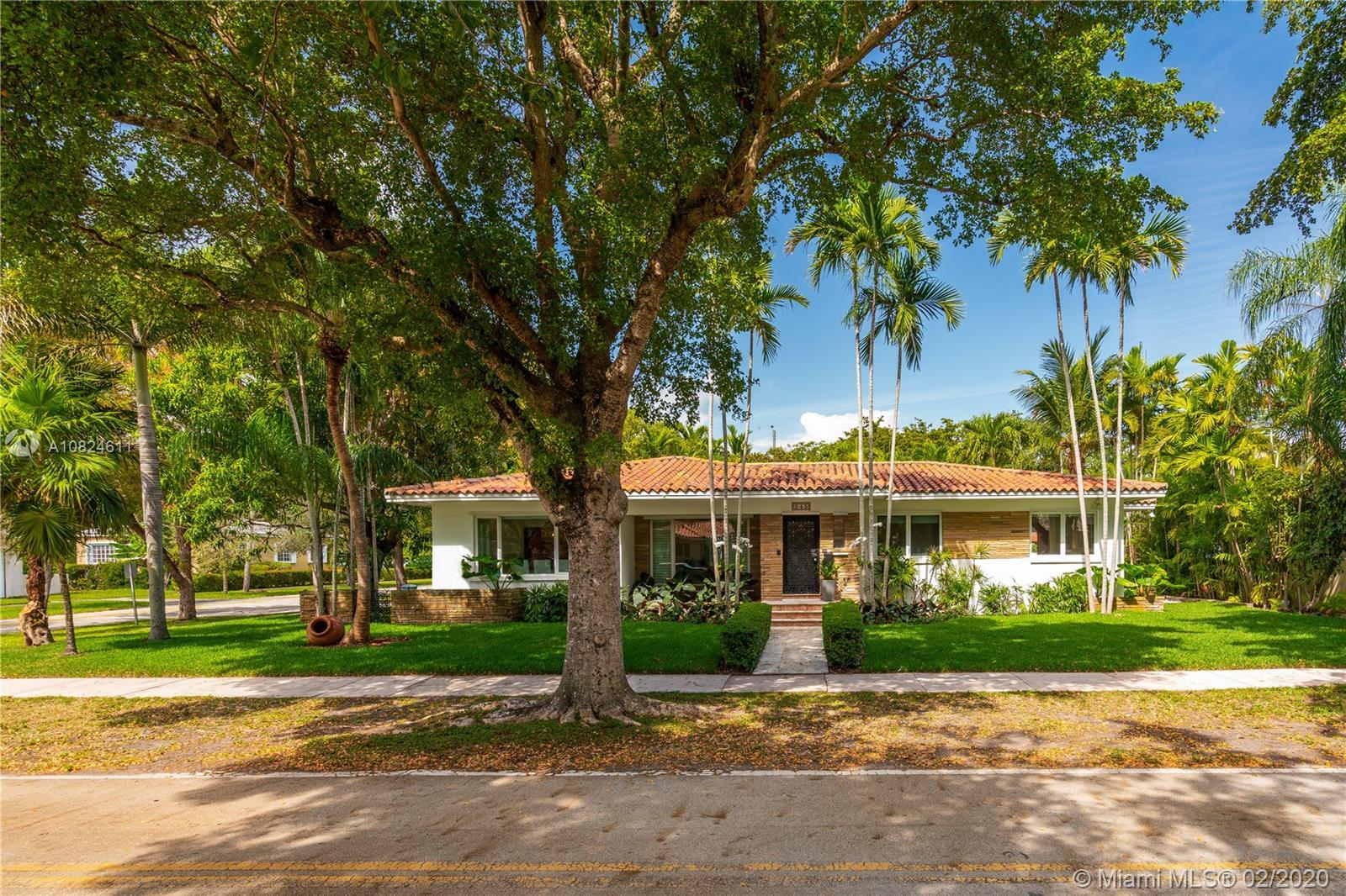 A Mid-century modern Coral Gables home sits on a 10,000' corner lot on a tree-lined street minutes a