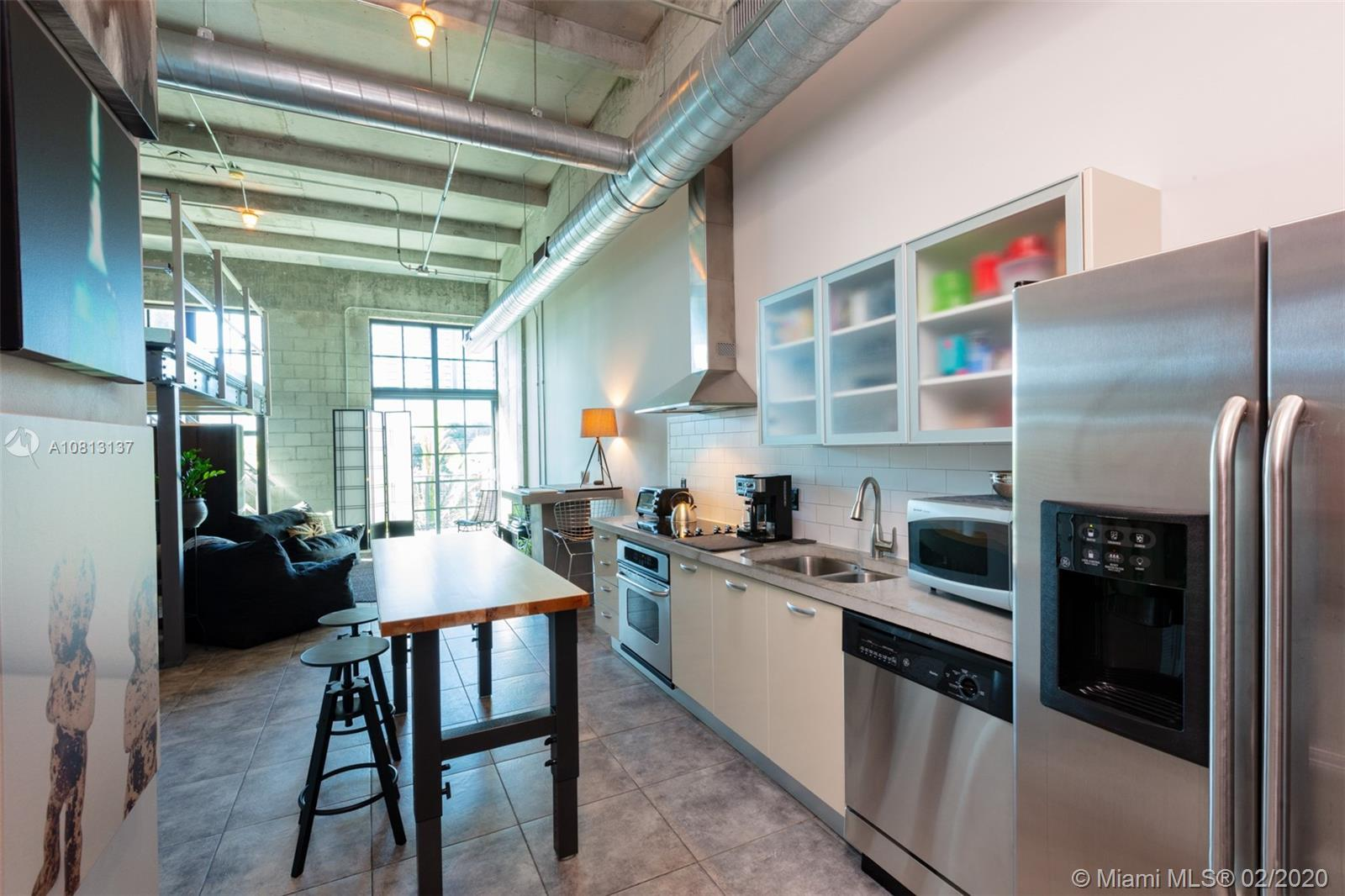 NY Style Industrial Loft with 15 ft ceiling height, stainless steel kitchen appliances and Italian K