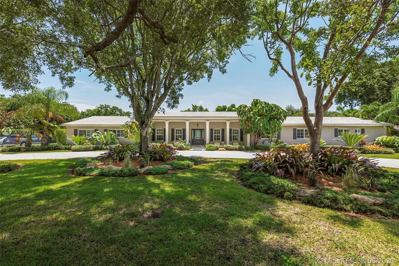 Warm, inviting, and impeccably maintained Pinecrest acre estate surrounded by majestic oaks on perfe