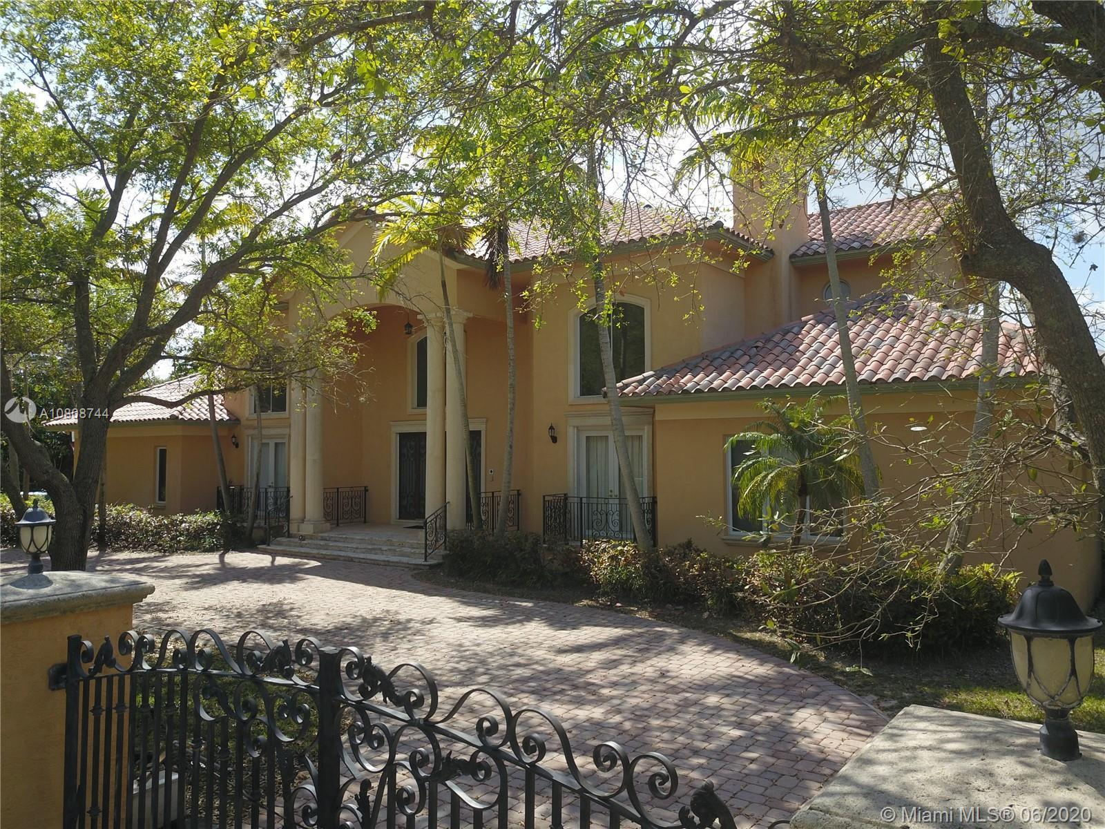Waiting for your personal touches is this exquisite Pinecrest two story Mediterranean Estate. Walled