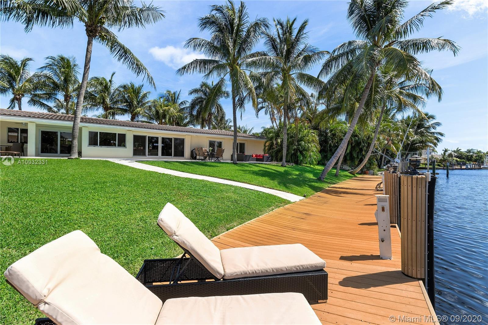 Perched above the Kingfisher canal, this extraordinary property on a rare oversized, deep-water lot