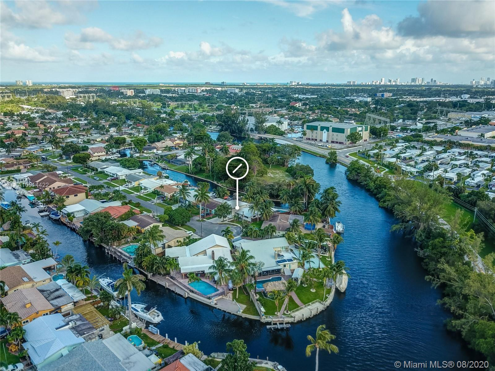 Commandingly situated on a sprawling lot in coveted Melaleuca Gardens, this transcendent waterfront