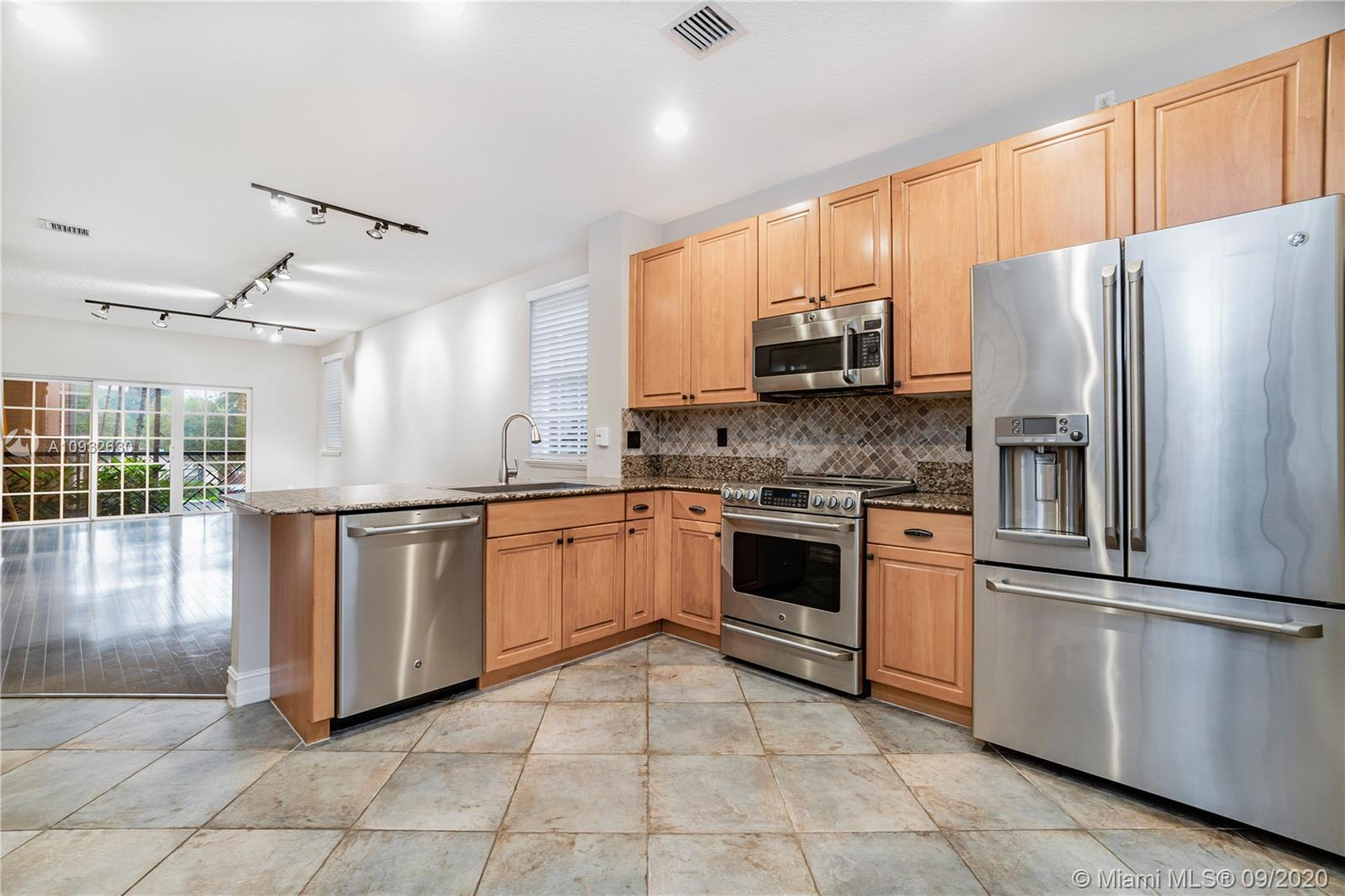 This beautifully maintained tri-level, 2 / 2.5 townhouse with a bonus room on the first floor featur