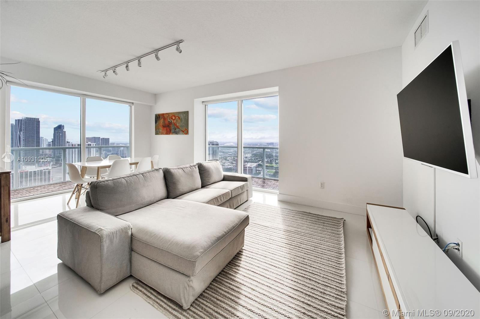 Soar above Miami in this 43rd floor, spacious corner unit w/ a large wraparound terrace & stunning v