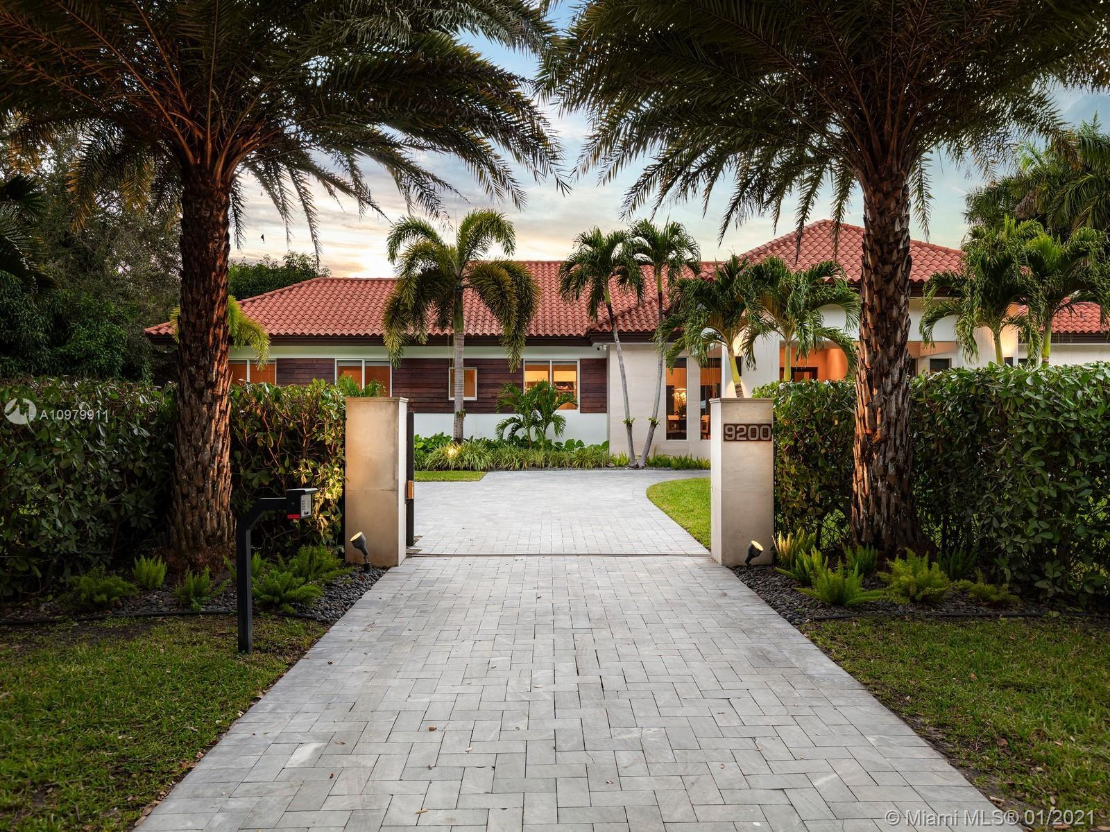 Impeccably pristine estate located in N Pinecrest, nestled on a 33,976 sf gated lot, surrounded by m