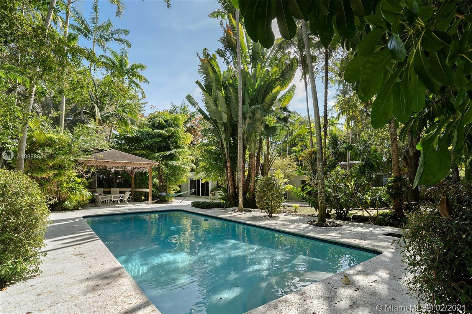A steal in North Pinecrest located on a magnificent and tranquil street. Enter this walled and gated