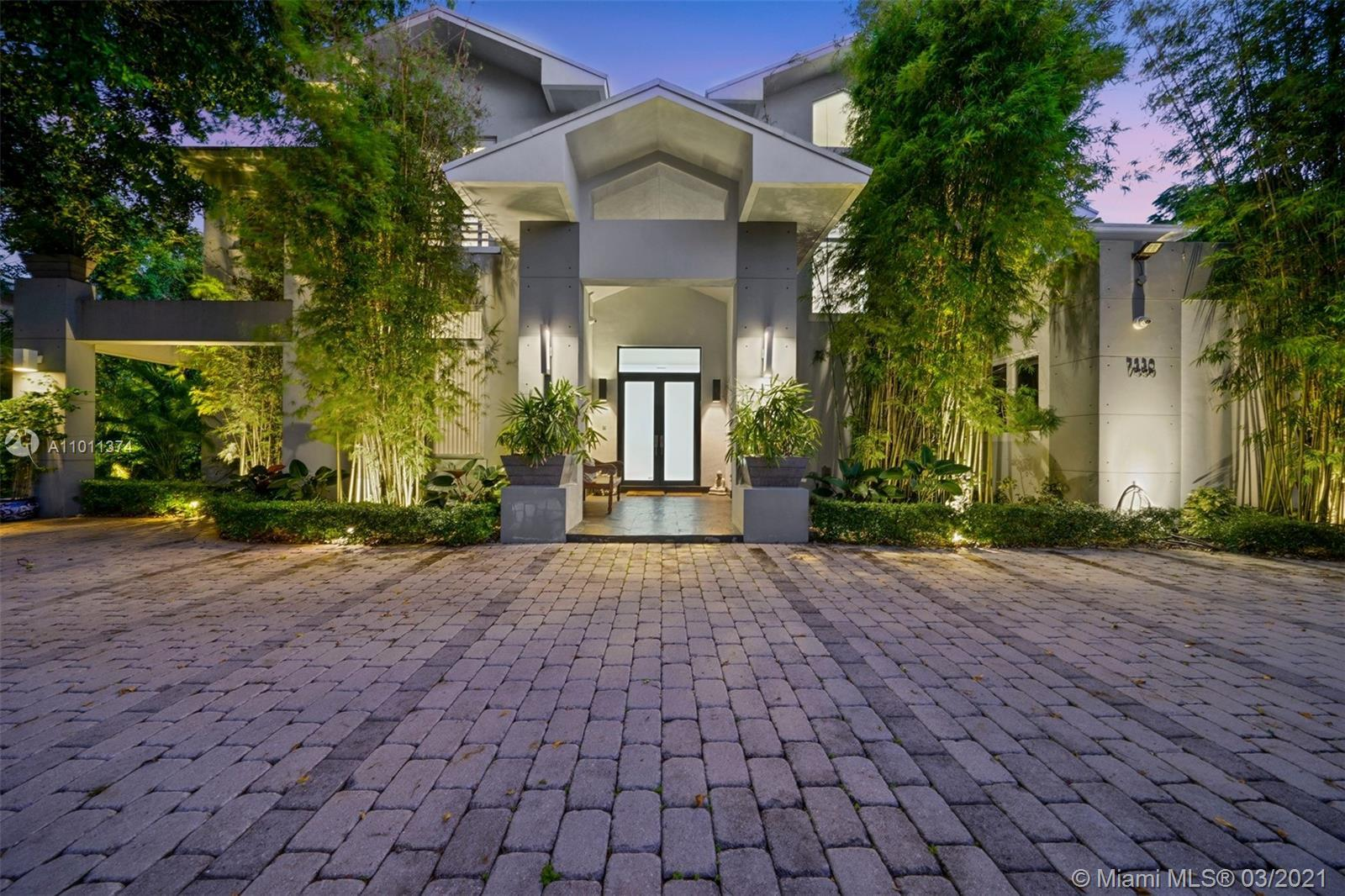 Prestigious contemporary residence nestled in the heart of North Pinecrest. Features double height l