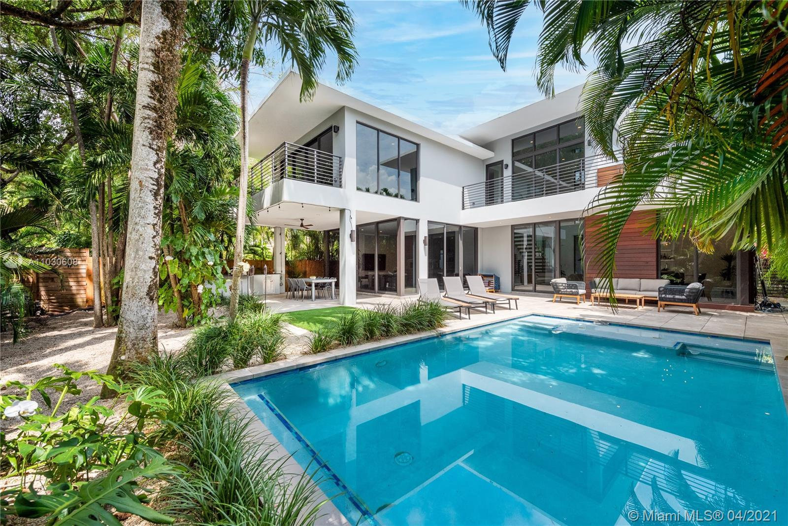 Fall in love with this Tropical Modern masterpiece in North Coconut Grove. Step inside and you're im