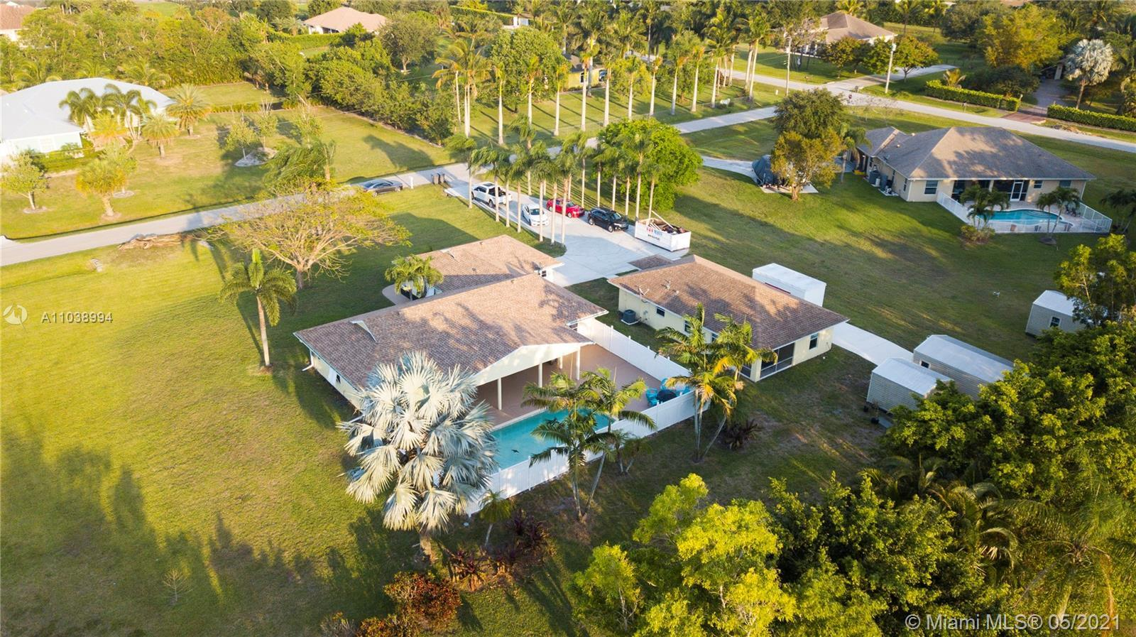 A long driveway flanked by royal palms lead to this gem with a spacious setback,on a 1+ acre lot. On