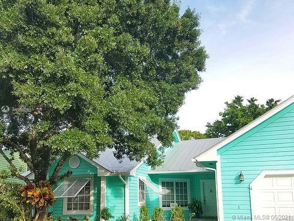 THIS BEAUTIFUL ONE STORY KEY WEST STYLE HOME HAS VOLUME CEILINGS AND IS FILLED WITH NATURAL LIGHT. T