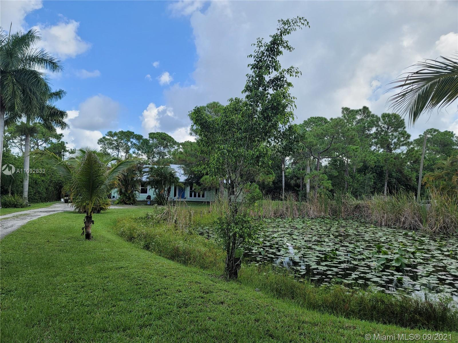 Jupiter Farms home on a large 1.25 acre pond lot, NEW roof, drain field, impact windows, updated 2nd