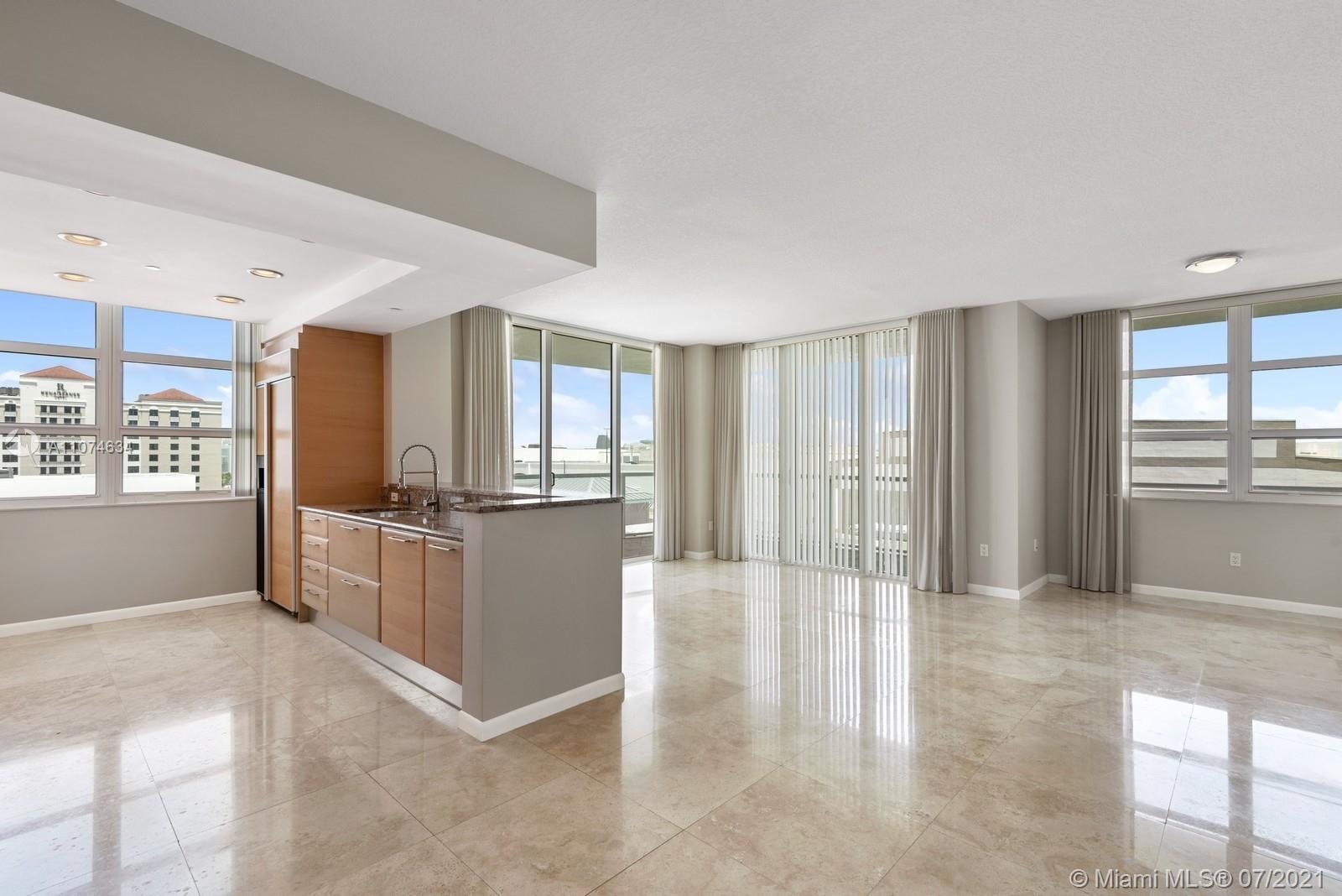 Luxury corner condo featuring walls of floor to ceiling glass, polished marble floors, wrap around g