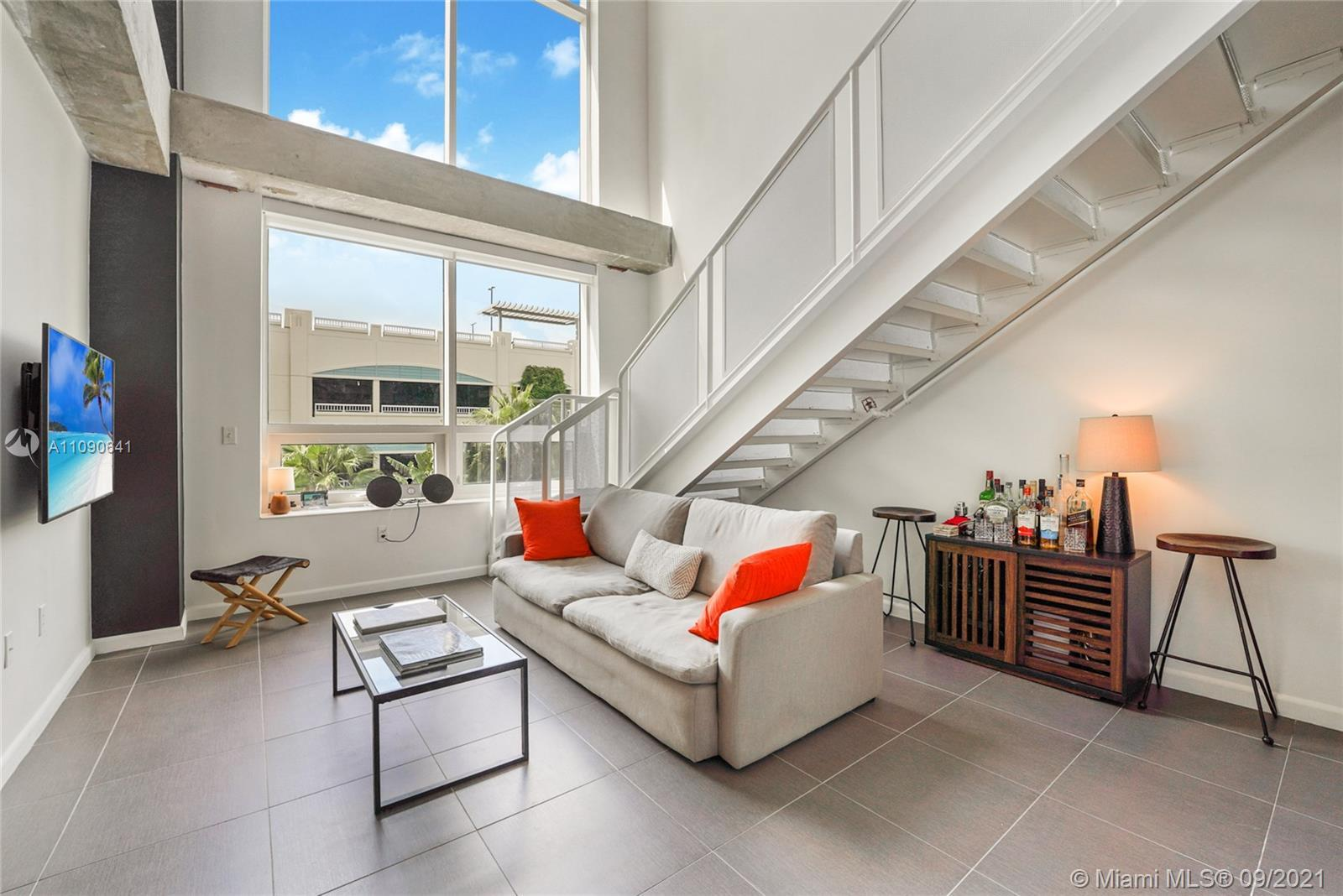 Modern and spacious loft with industrial details, soaring-high ceilings, two balconies, custom light