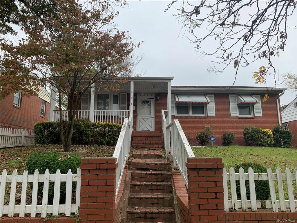 This brick ranch home features three bedrooms, one of which has been opened to the front room to aff