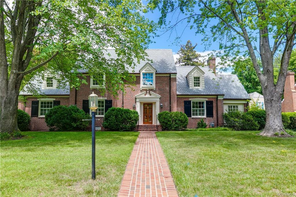 Stunning sun-filled Family Room addition with stone fireplace + wet bar complete this classic brick