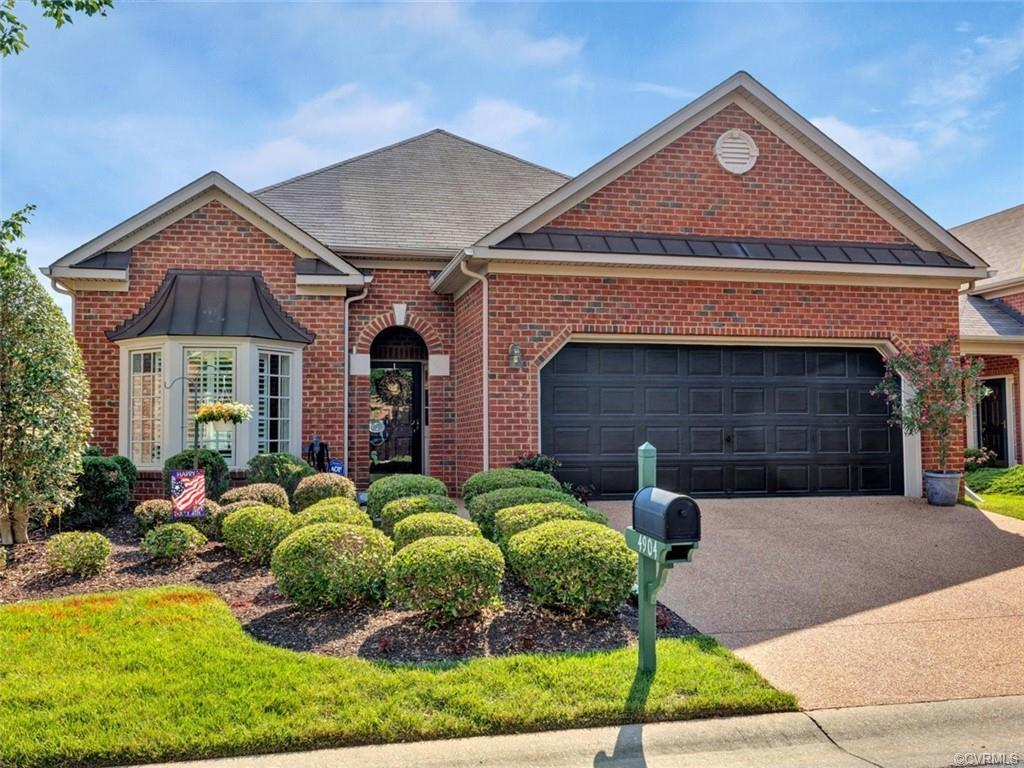 All brick exterior custom home by Boone with aggregate patio and driveway. Patio has powered retract