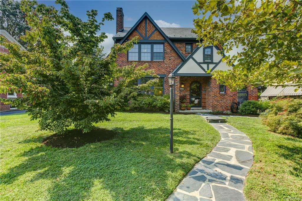 This brick-and-slate Tudor in the sought-after Bellevue neighborhood has everything you're looking for – eye-catching architectural flair, almost 2,000 square feet of living space and a 1/3-acre lot to relax on. The first level features formal living and dining rooms with exceptional stained woodwork, including ceiling beams in both rooms and a fireplace with a paneled chimney breast in the living room. Rounding out the first level is a sun-filled family room, a tiled bath, an enclosed side porch with a slate floor and a previously renovated kitchen with raised-panel cabinets, granite countertops, a stainless sink and an island. The second level has three bedrooms and a renovated hall bath. Oak floors. Two-zone heating and cooling. Walk-up attic; full lower level with a utility area. Concrete driveway. The fenced backyard has a large deck for outdoor entertaining, as well as a garden shed. Just move in and plant your English garden.